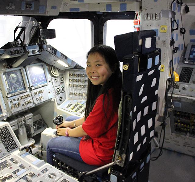 Bridget sits inside the cockpit of a space shuttle mockup.