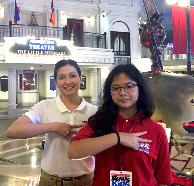 "Pinky Laurena, Minister of Visitor Experience at KidZania Manila, and Georgia gesture ""hello,"" or ""kai,"" the KidZania way."