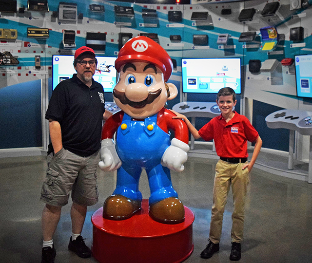 "Preston and the museum co-founder, Joe Santulli, pose with Mario in the ""Timeline of Consoles"" room."
