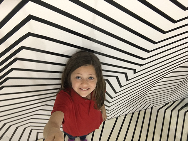 Kid Reporter gets creative in an optical illusion room.