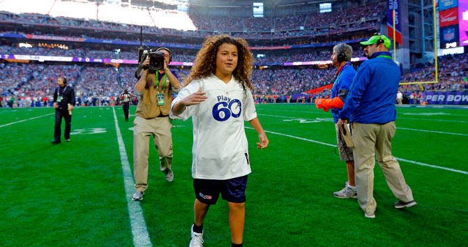 Bobby Sena, winner of this year's NFL PLay 60 Super Kid contest, runs across the field before Super Bowl XLIX.