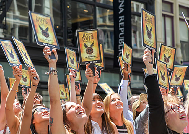 """Scholastic """"Muggle Mob"""" participants raise their paddles as the banner announcing the new Harry Potter story is lowered."""