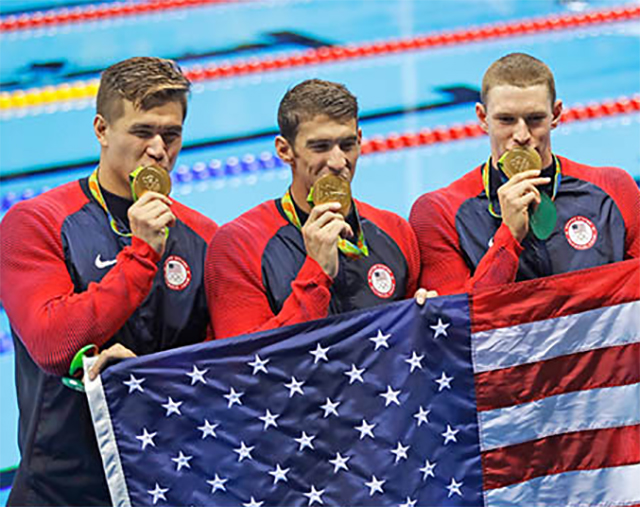 Nathan Adrian, Michael Phelps, and Ryan Murphy display their gold medals during a victory lap after winning gold in the 4 x 100-meter medley relay final, the last men's swimming competition at the 2016 Summer Olympics.