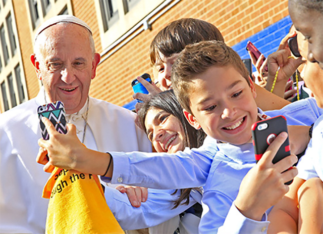Pope Francis greets students at Our Lady Queen of Angels School in East Harlem on September 25. The Pope got a lesson in how to use smartphones.