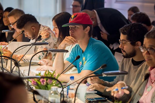 Screenwriters, directors, and actors, including Ansel Elgort (in red cap), critique the work of Ghetto Film School students.