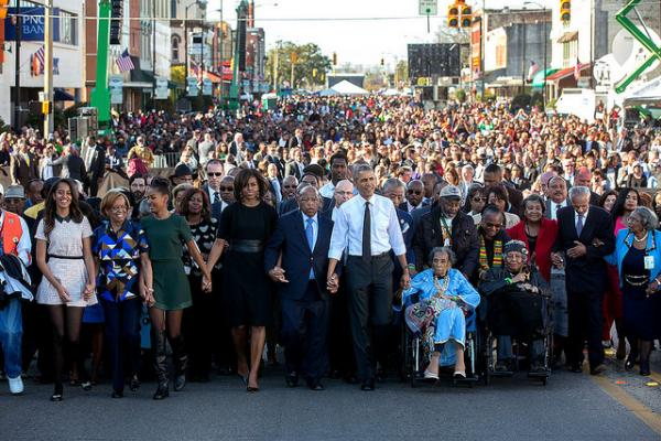 President Barack Obama and First Lady Michelle Obama join hands with Rep. John Lewis, D-Ga. as they lead the walk across the Edmund Pettus Bridge to commemorate the 50th Anniversary of Bloody Sunday and the Selma to Montgomery civil rights marches