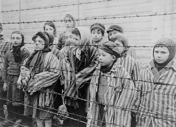 Child survivors of Auschwitz, wearing adult-size prisoner jackets, stand behind a barbed wire fence.