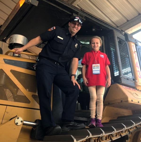 Ella and Captain Scott Kenney stand on a bulldozer that Cal Fire uses to fight wildfires.