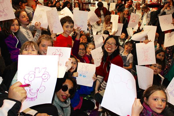 Young fans of Grace Lin hold up their dragon drawings at a book-signing event in Dedham, Massachusetts.