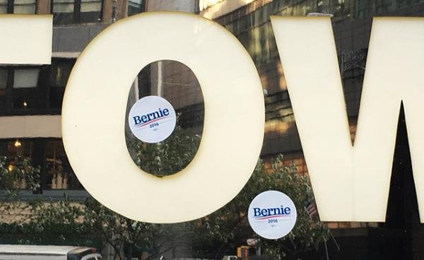 Bernie Sanders stickers on a Trump Tower sign. The New York City building is owned by Republican candidate Donald Trump.