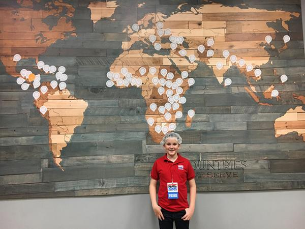 Ryan in front of a map of countries served by Feed My Starving Children