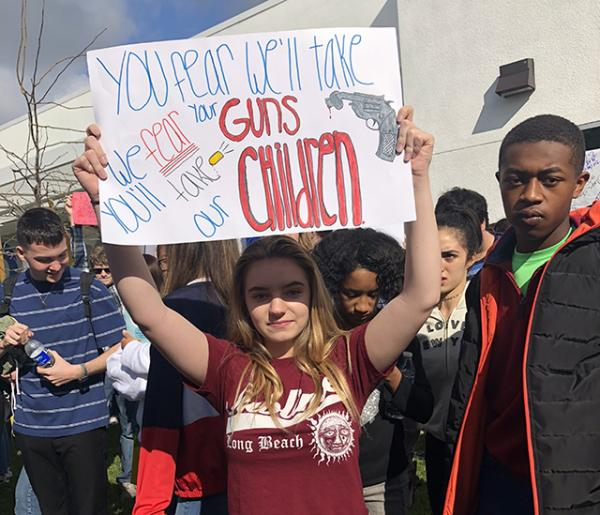 16-year-old sophomore Haley Gilson stands with a poster, expressing her views on gun control