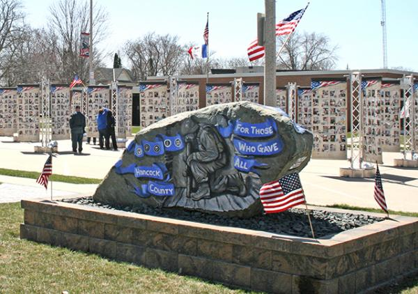 Photo of the memorial towers with Hancock County's Freedom Rock in front.