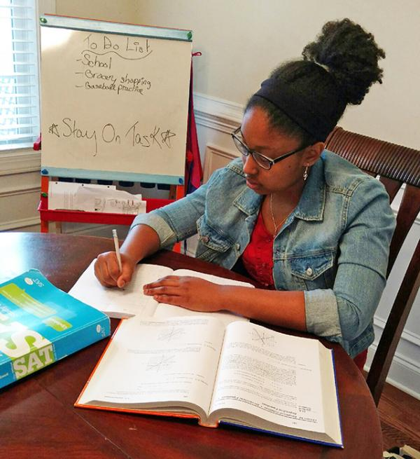 Kayla studies at her dining room table.