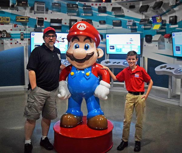 "Preston Phillips and NVM co-founder, Joe Santulli, pose with Mario in the ""Timeline of Consoles"" room."
