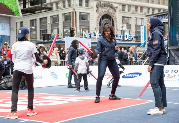 First Lady Michelle Obama participates in a fencing demonstration with Ibtihaj Muhammad of the U.S. Olympic Fencing Team during the 2016 Olympics 100 Days Out event in Times Square, New York, N.Y., April 27, 2016.