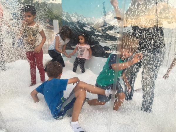 Logan and Jude Bialski playing in fake snow outside the House of Switzerland