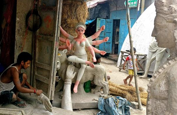 An artisan sculpts the hand of an effigy in the labyrinthine streets of Kumartuli