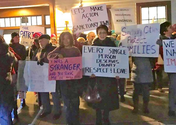 Local residents express support for making Acton, Massachusetts, a sanctuary city after President Trump instituted a temporary ban on people entering the United States from several predominately Muslim countries.