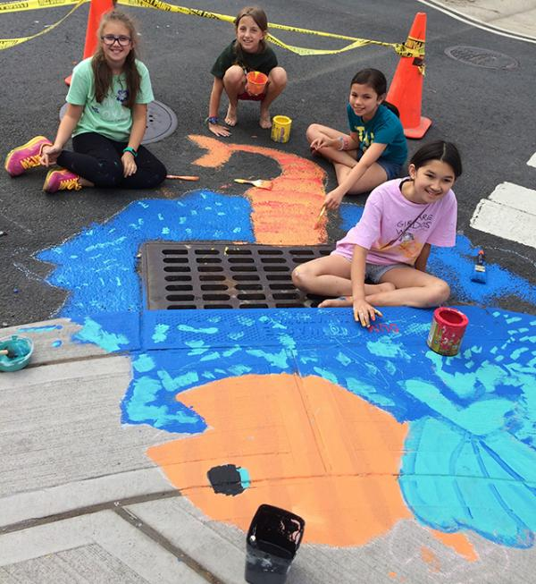 Girl Scout Troop 12881 painting a storm drain mural in Hoboken, NJ.