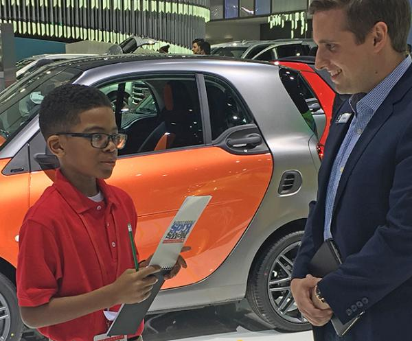 Titus learns about cars at the Detroit auto show.