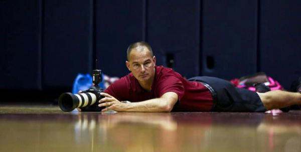 Josefczyk sprawled on the floor with his equipment to get a great shot at a basketball game.