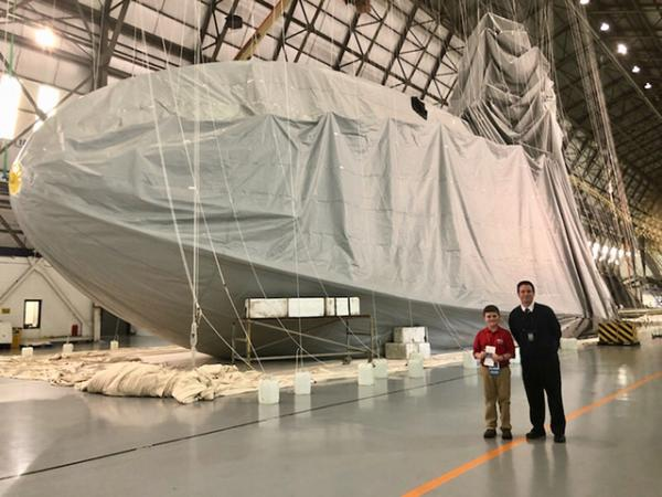 Nolan and senior pilot James Kosmos Jr. stand in front of a Goodyear Blimp currently under construction in Mogadore, Ohio.