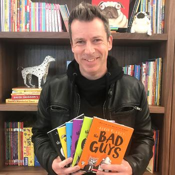 Aaron Blabey, who recently visited the United States from his home in Australia, displays books from his bestselling Bad Guys series.