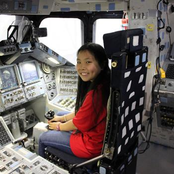 Bridget sits inside the cockpit of a space shuttle mockup.