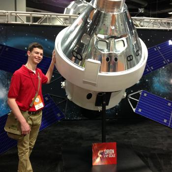 Erik Weibel in front of the ¼ scale Orion Spacecraft model. The Orion will carry a crew of 4 humans to Mars.