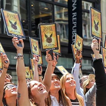 "Scholastic ""Muggle Mob"" participants raise their paddles as the banner announcing the new Harry Potter story is lowered."