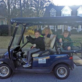 A Peachtree City family enjoys a ride on a golf cart.
