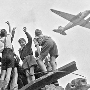 German children stand atop a ruined building in the western section of Berlin in 1948, cheering as a U.S. cargo plane arrives with food, fuel, and other supplies. Many children also got candy.